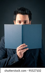 Young man behind a book against dark background.