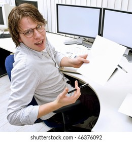 A young man behind a desk in an office, turning around to ask for help, holding a blank piece of paper for your message