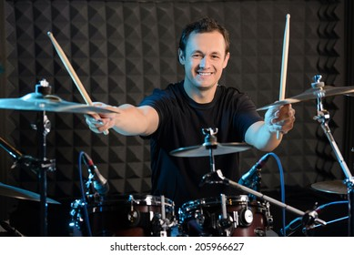 Young man behind drum-type installation in a professional recording studio