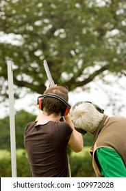Young man being instructed in clay shooting on the shooting range