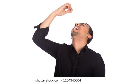 Young man bending his head back raising a hand like holding invisible grapes open his mouth to eat, isolated on a white background.