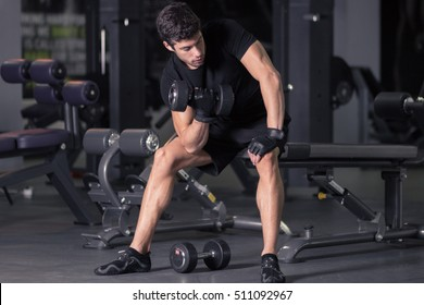 young man biceps curls sitting. Indoors gym dark.