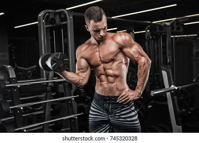young man biceps curls sitting. Indoors gym dark.