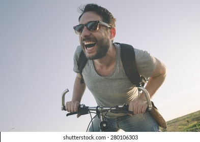 Young man with bicycle having outdoor fun. retro vintage style image. Happy hipster guy smile while riding bike on the road. Cycling and adventure traveling lifestyle.