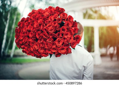 Young man with big bouquet of roses outdoor