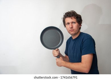 A young man with a big frying pan on a white background. Concept of play tennis, household work for men, feminism.