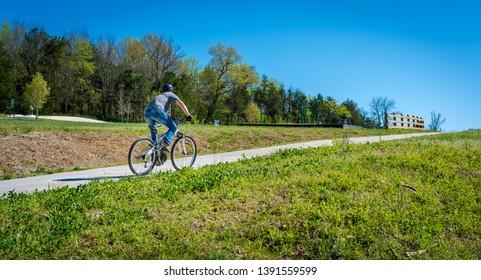 Young man biking on bike trail in Bella Vista, Northwest Arkansas