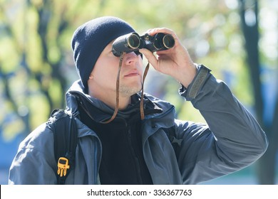 Young man with binoculars is bird watching at demi-season natural background