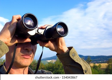Young man with binoculars watching birds in nature, Man with binoculars, photography