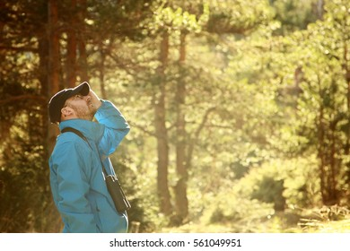 A young man birdwatching in the forest early morning