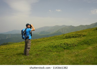 Young man is birdwatching and trekking in the Central Balkan Mountains in Bulgaria. The man is birding  eagles and falcons.