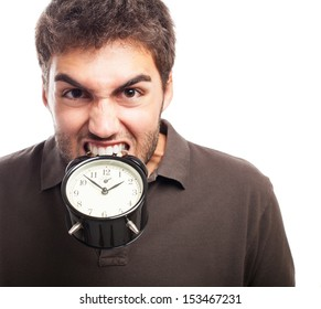 young man biting an alarm clock on a white background