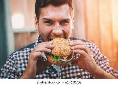 Young man biting fresh tasty hamburger and looking at camera