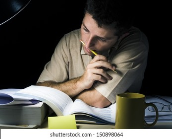 Young Man Biting Pencil Studyng at Night isolated on black background