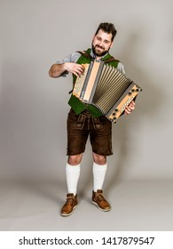 young man with black beard and leather trousers and traditional costume and accordion is posing in front of grey background