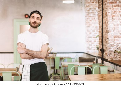 Young man in black cap,white t-shirt and apron standing and dreamily looking in camera while working in cafe
