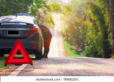 Young man with a black car that broke down on the road