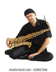 A young man in black clothes, black cap, wearing glasses, sitting and holding his saxophone in his lap, looking into camera - isolated on white