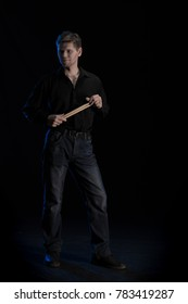 A young man in black clothes playing with drumsticks and posing on a black background with blue light