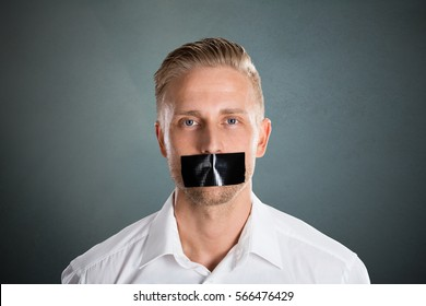 Young Man With Black Duct Tape Over His Mouth Against Grey Background