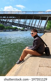 young man in black glasses resting on the River Seine, Paris, France