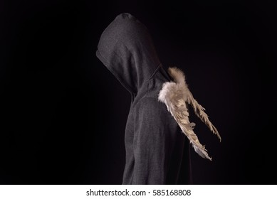 Young man with black hoodie and white feathered wings behind the back on a dark background. Conceptual photo, good and bad