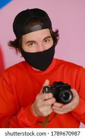 A young man in a black protective mask and in a red sweatshirt holds a mirrorless camera in his hands. Male photographer uses a mirrorless camera to take a picture.