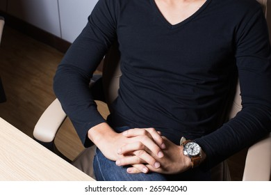 Young man in black shirt on the chair in working room