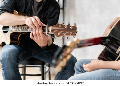 Young man in black shirt teaches his younger brother to play guitar chords correctly
