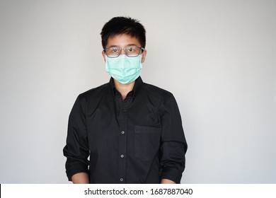 The young man in black shirt wearing face hygienic mask.  Protect global covid-19 virus pandemic. The corona-virus from wuhan is dangerous.