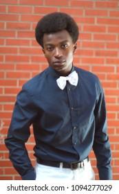 young man black shirt white bow tie brick wall