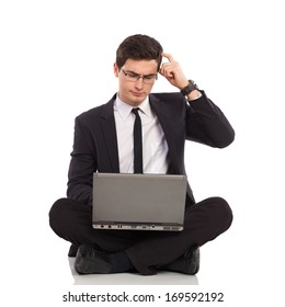 Young man in black suit holds laptop on his crossed legs and thinking. Full length studio shot isolated on white.