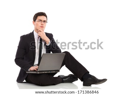 6890fd8976 Young man in black suit holds laptop on his leg and thinking. Full length  studio