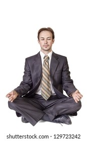 Young man in black suit meditating on white background