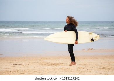 Young man in black wetsuit walking in the beach with surfboard on daytime