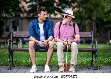 Young man and blind senior with white cane sitting on bench in park in city.