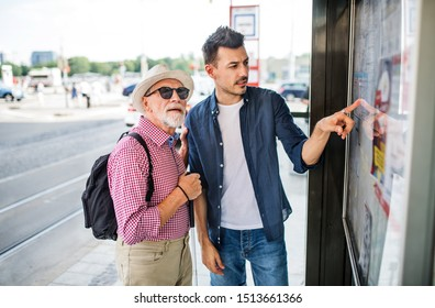 Young man and blind senior with white cane at bus stop in city.