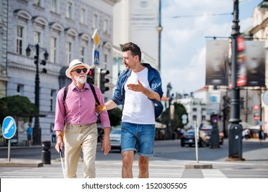 Young man and blind senior with white cane walking in city, crossing street.