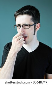A young man blocks his nose after smelling something bad.