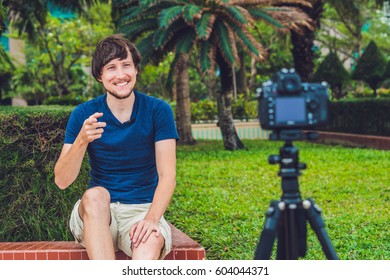 Young man blogger records video in front of the camera in the park. Blogger concept