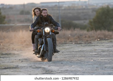 young man and blond woman driving motorbike classic