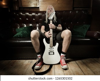 Young man with a blonde hair holding guitar and sitting on sofa in pub