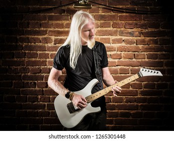 Young man with a blonde hair playing guitar in pub
