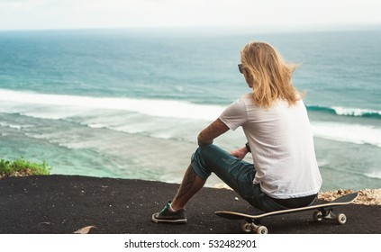 Young man blonde skater sitting in front of amazing ocean view