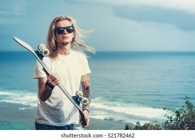 Young man blonde in sunglasses skater in front of amazing sea view