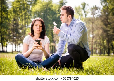 Young man blowing dandelion to face of his girlfriend holding mobile phone