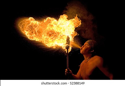 Young man blowing fire from his mouth