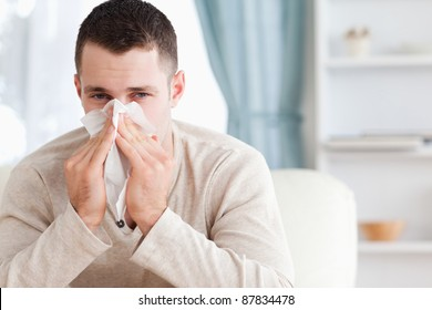 Young man blowing his nose in his living room