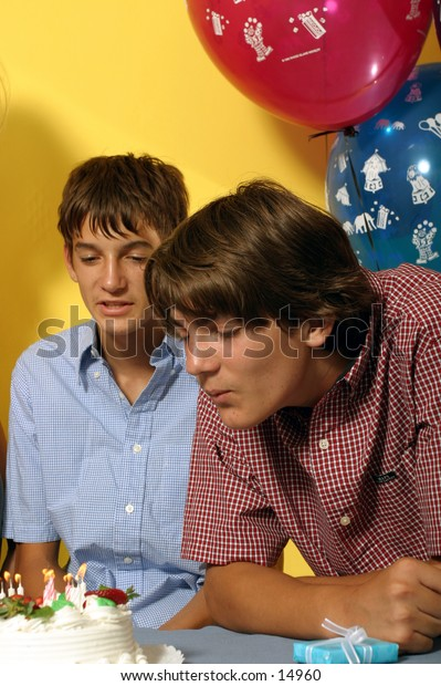 young man blowing out candles