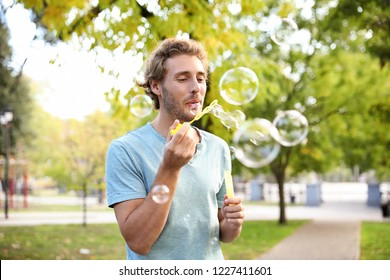 Young man blowing soap bubbles in park